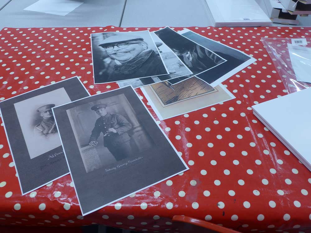 Copies of black and white archive pictures on a table with a red and white spotted tablecloth