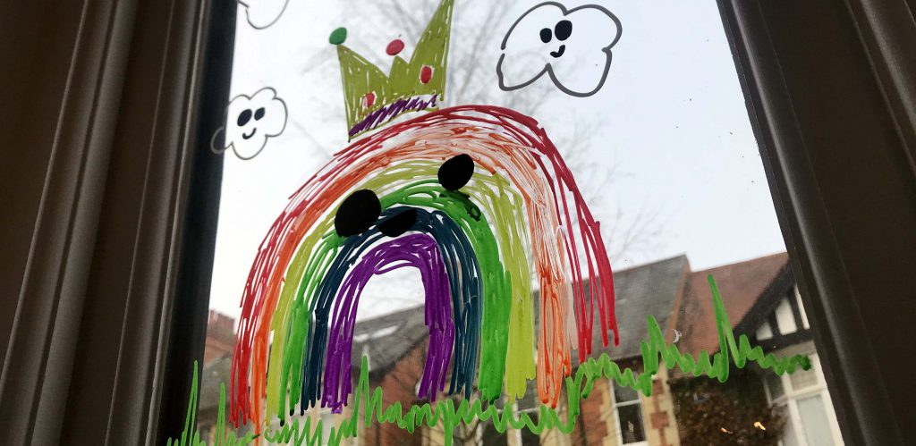 A colourful smiling rainbow drawing on a winodw, with red brick houses in the background