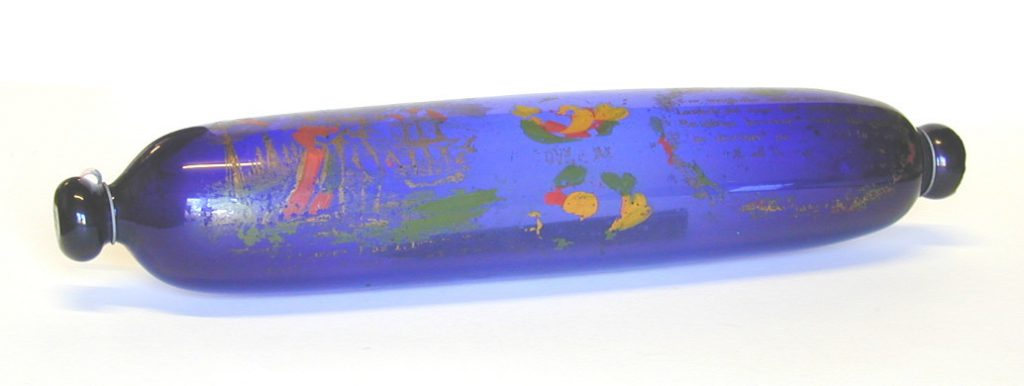 A rolling pin, made from blue glass. It is decorated with green, gold and red paintwork.