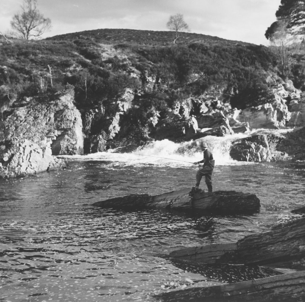 A black and white image of a man flyfishing on a river. He is standing on an island of rocks in the middle of the river.